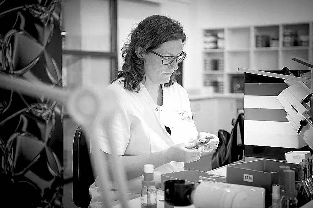 Een medewerker uit de optische techniek is een bril aan het maken