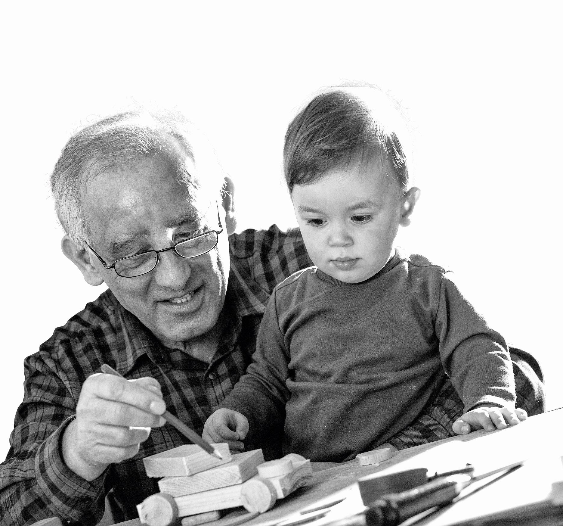 Opa en kleinzoon die samen aan het puzzelen zijn