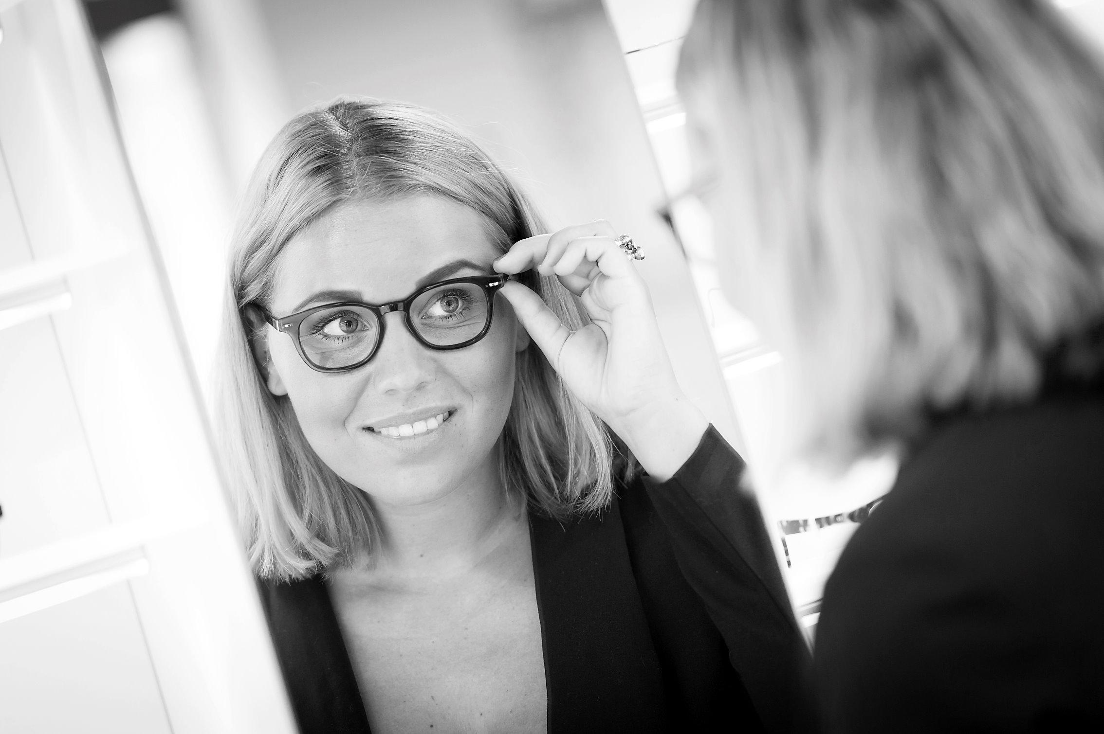 Een vrouw kijkt in de spiegel naar haar nieuwe bril
