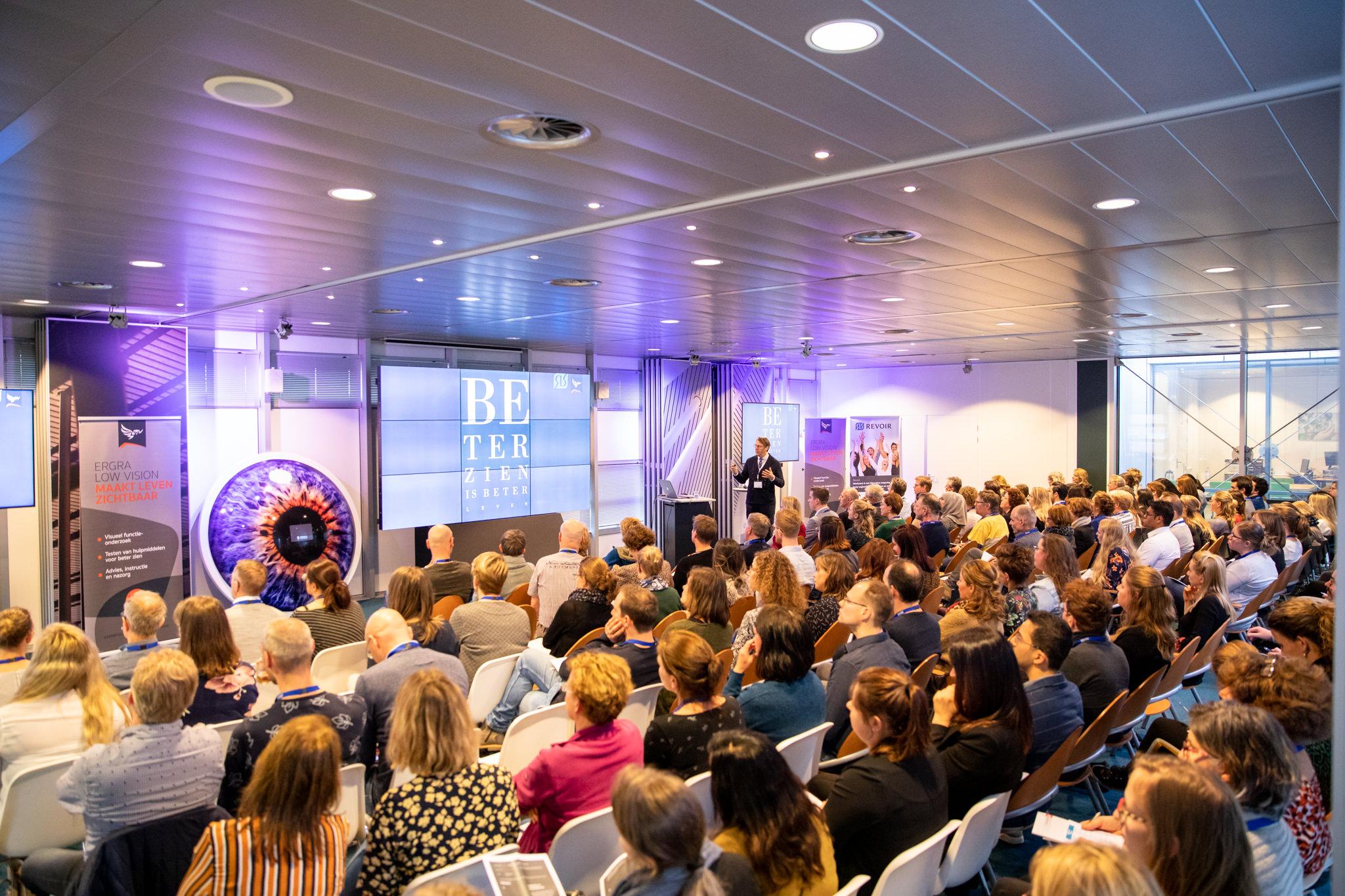Een zaal vol met Revoir Academy deelnemers luistert naar een presentatie