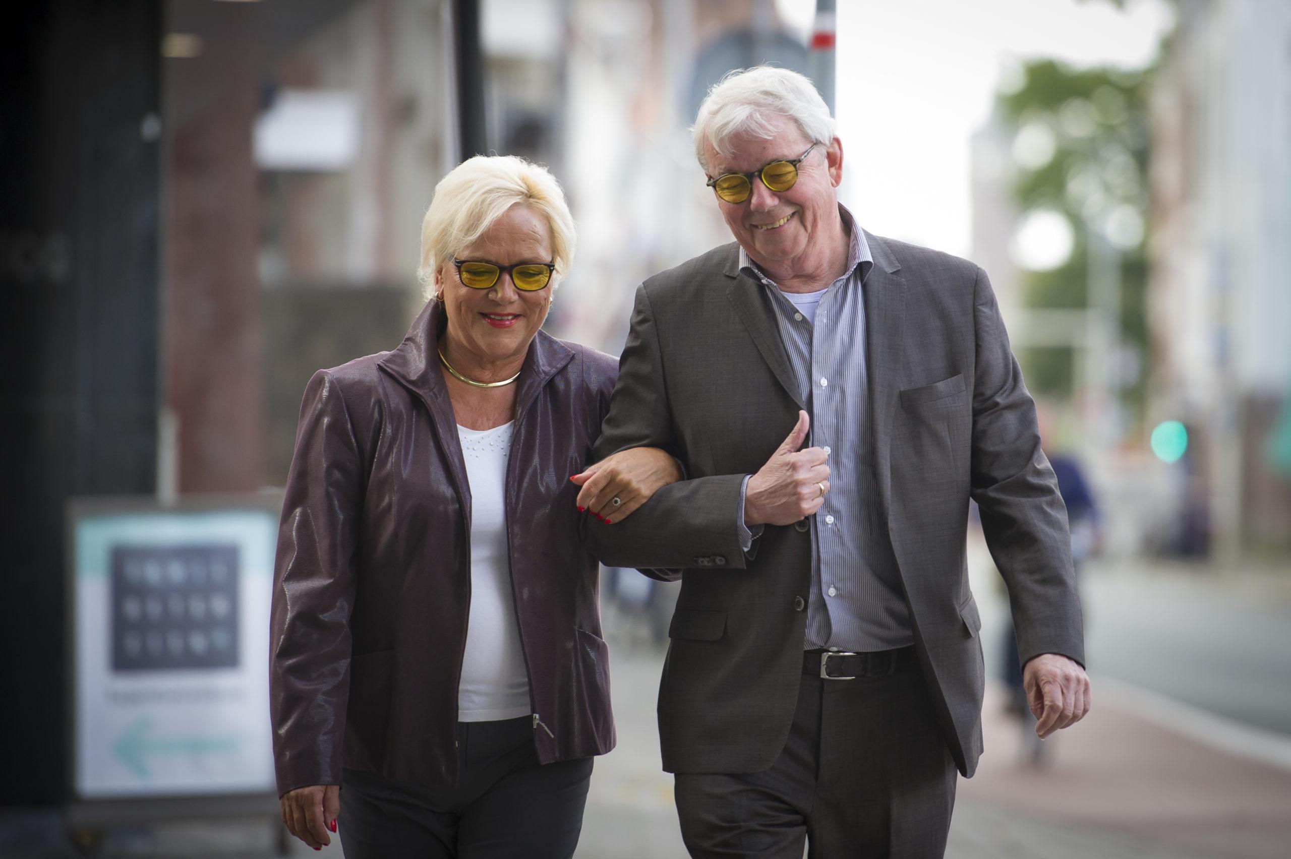 twee blije klanten lopen arm in arm over straat met hun nieuwe E-scoopbril